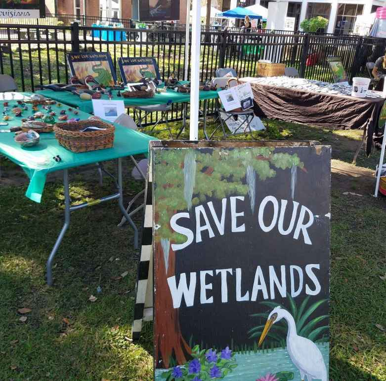 Informational table with a sign reading Save our Wetlands
