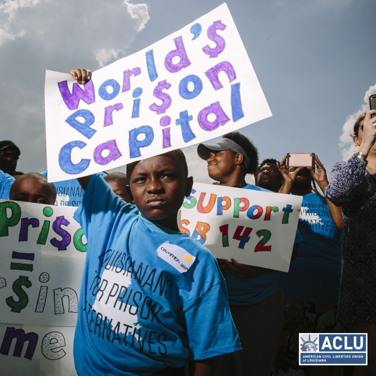 Photo of Black boy holding sign that says World's Prison Capital
