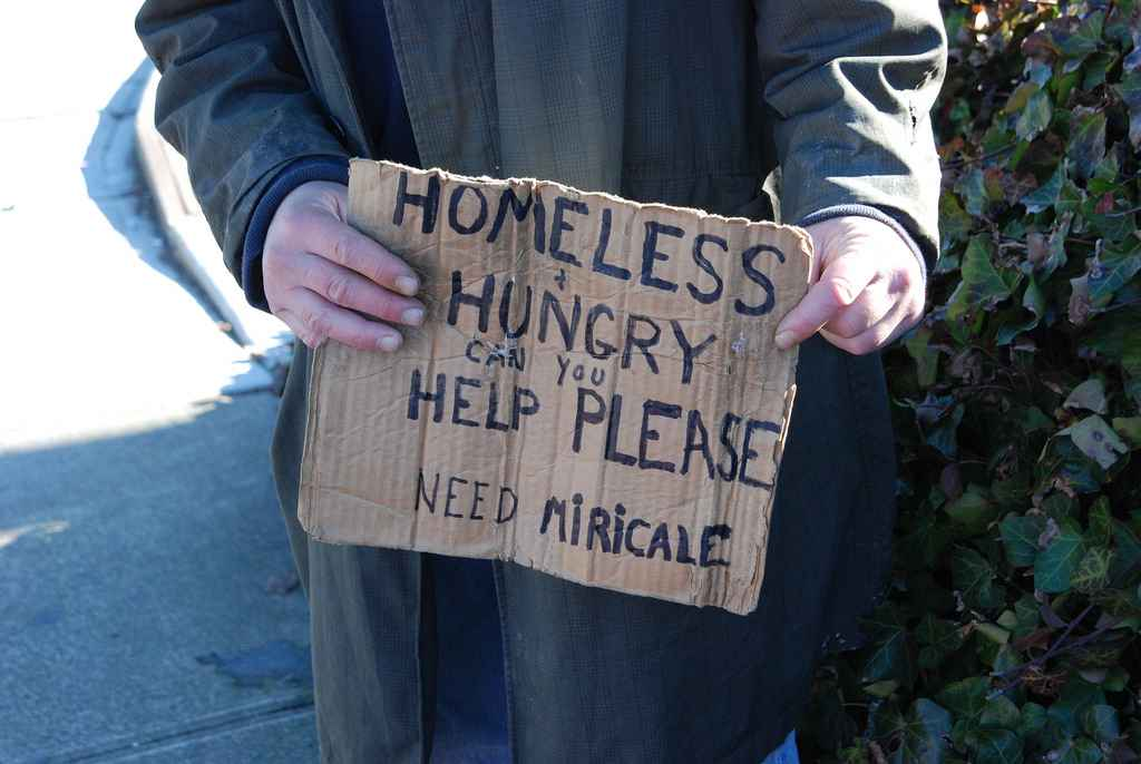 homeless man holding sign asking for help