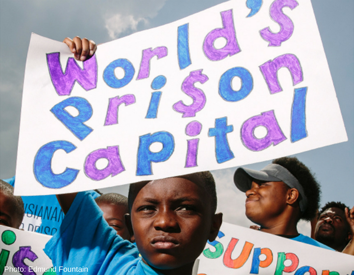 "Photo of a young Black boy holding up a sign that reads ""World's Prison Capital"""