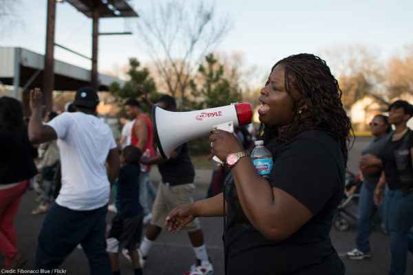 A Black woman speaking into a bullhorn at a protest