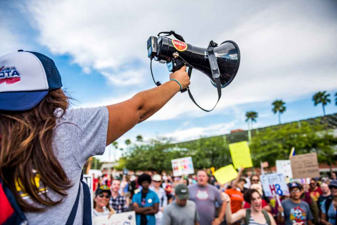 Student holding up a megaphone in front of a crowd