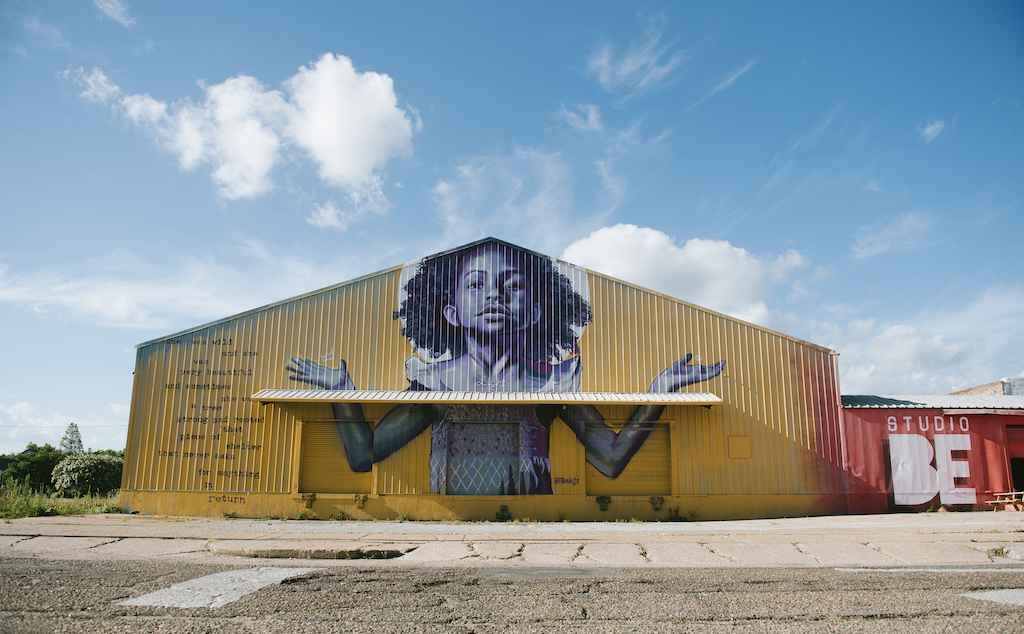 The exterior of BMike's Studio Be, with a mural of a young Black girl with her arms outstretched