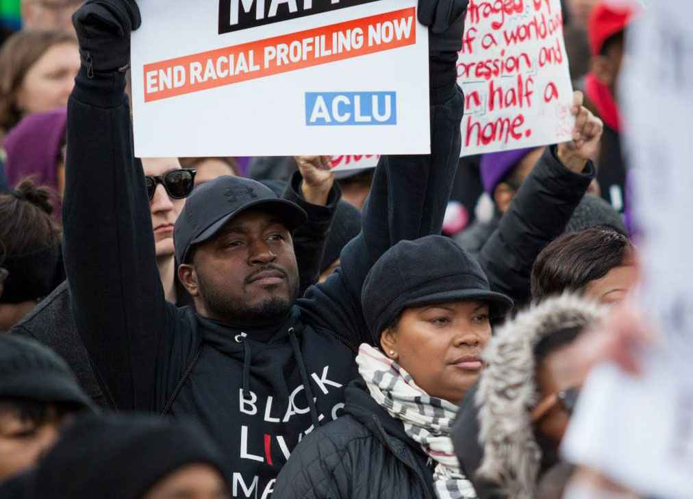 "Black man holding a sign that reads ""end racial profiling now"""