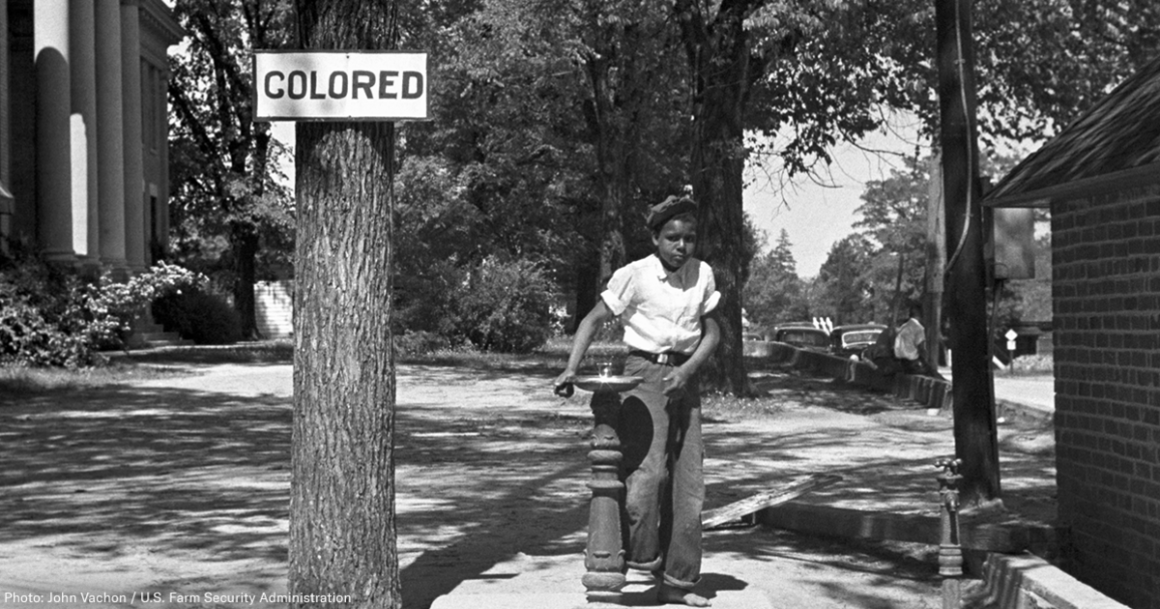 "A Black boy stands next to a water fountain marked ""colored"" in this historical photo"