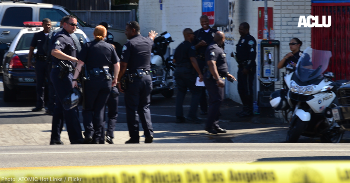 a group of police officers gathers outside a convenience store
