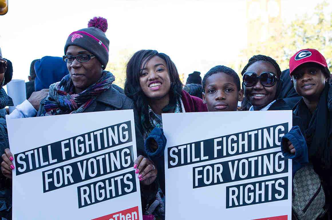 "Group of Black young hold signs reading ""Still fighting for voting rights"""
