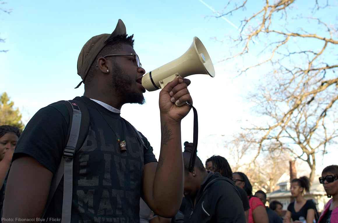 A black man holds a bullhorn at a protest