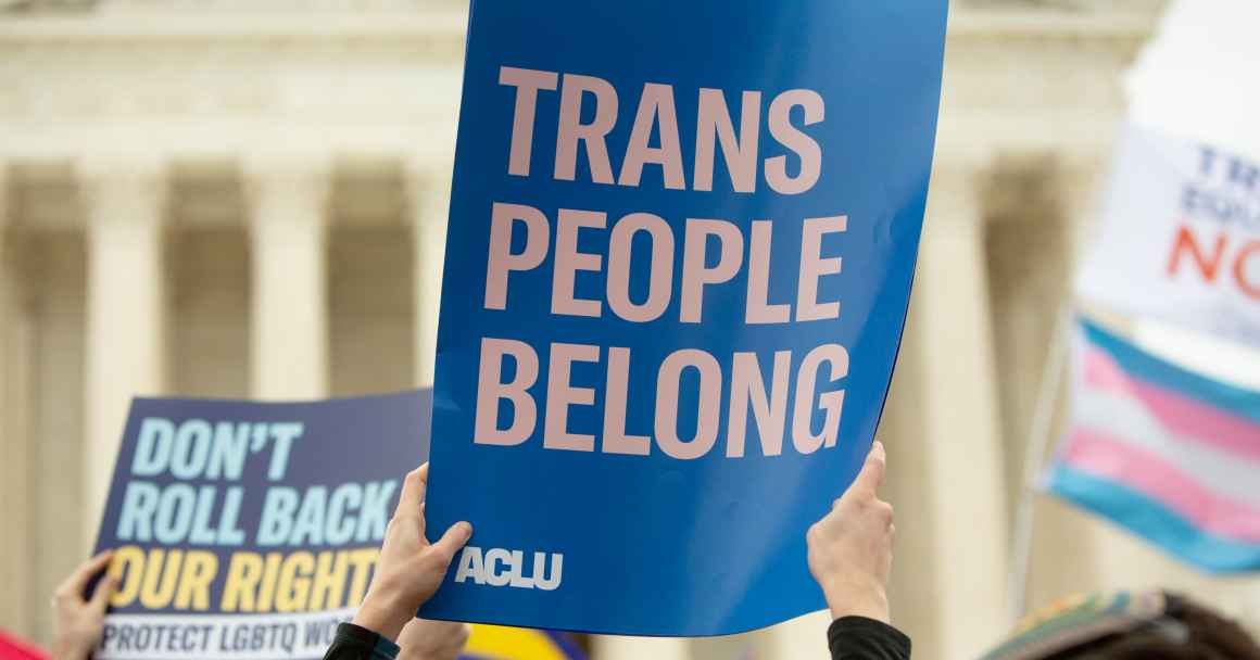 """A rally sign outside the Supreme Court reads """"trans people belong"""""""